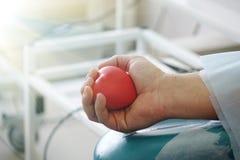 Coeur rouge dans les mains du donateur images libres de droits