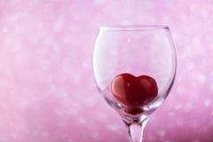 Coeur rouge dans un verre sur le fond brouillé Photos libres de droits