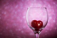 Coeur rouge dans un verre sur le fond brouillé Photographie stock libre de droits