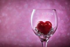 Coeur rouge dans un verre sur le fond brouillé Photographie stock