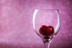 Coeur rouge dans un verre sur le fond brouillé Images libres de droits