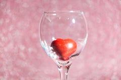 Coeur rouge dans un verre sur le fond brouillé Image stock