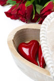 Coeur rouge dans une boîte en bois et des roses Images stock