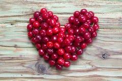 Coeur rouge de cerise sur la table en bois Images libres de droits