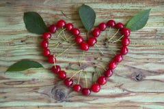 Coeur rouge de cerise sur la table en bois Photo stock