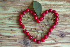 Coeur rouge de cerise sur la table en bois Photographie stock libre de droits