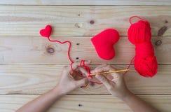 Coeur rouge de crochet fait main sur le fond en bois Image stock