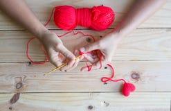 Coeur rouge de crochet fait main sur le fond en bois Photo stock