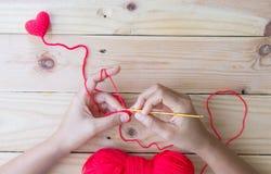 Coeur rouge de crochet fait main sur le fond en bois Photos libres de droits