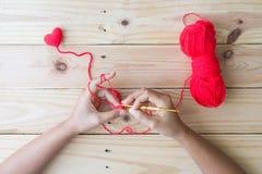 Coeur rouge de crochet fait main sur le fond en bois Photographie stock