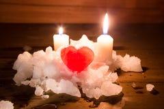 Coeur rouge de glace sur une neige petit groupe sur les conseils en bois et le bureau deux Photo stock