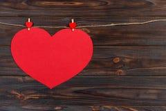 Coeur rouge de grand amour accrochant sur le fond en bois de texture, concept de carte de jour de valentines Image stock