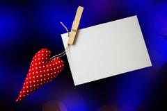 Coeur rouge de jouet et carte vierge sur le noir Images stock