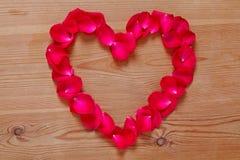 Coeur rouge de pétale de rose sur le fond en bois. Image libre de droits