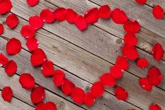 Coeur rouge de pétales de rose au-dessus de fond en bois Image libre de droits