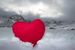 Coeur rouge de peluche dans la neige sur un fond des montagnes Photos stock