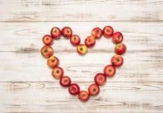 Coeur rouge de pommes au-dessus de fond en bois Concept d'amour Photographie stock