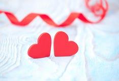Coeur rouge de ruban et deux coeurs sur le fond en bois bleu le Saint Valentin Image stock