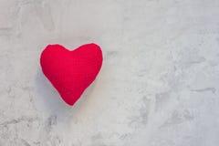 Coeur rouge de textile fait main sur un fond concret gris Photos stock