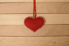 Coeur rouge de textile sur la bande sur une texture en bois Images libres de droits
