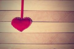 Coeur rouge de textile sur la bande sur une texture en bois Photos stock