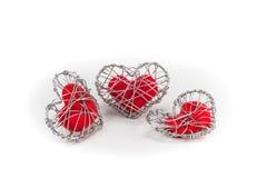 Coeur rouge de tissu dans la cage tricotée de fil Photographie stock libre de droits