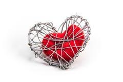 Coeur rouge de tissu dans la cage tricotée de fil Images stock