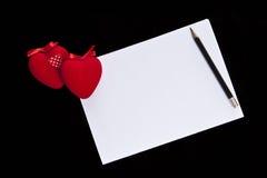 Coeur rouge de velours et feuille blanche sur un fond noir Photographie stock libre de droits