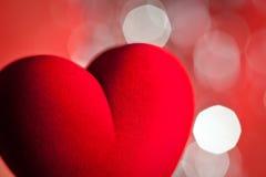 Coeur rouge de velours, lumières defocused sur le fond Images stock