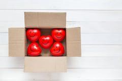 Coeur rouge de vue supérieure dans la boîte brune sur la planche en bois blanche Pour l'amour Image stock