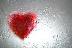 Coeur rouge derrière une fenêtre humide Photographie stock