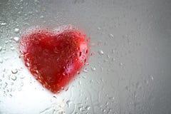 Coeur rouge derrière une fenêtre humide Image stock
