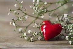 Coeur rouge des fleurs blanches en verre et petites sur le bois gris rustique Image libre de droits