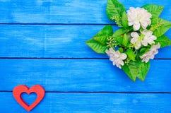 Coeur rouge en bois et fleurs vertes sur un fond en bois bleu Image libre de droits