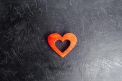 Coeur rouge en bois sur un fond concret gris Forme de coeur, une métaphore pour l'amour et sentiments humains Le concept de l'amo Photographie stock