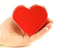 Coeur rouge en céramique dans une main masculine Image stock