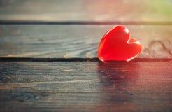 Coeur rouge en plastique sur le fond en bois Photos stock