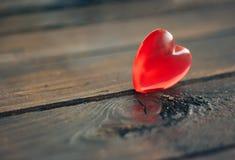 Coeur rouge en plastique sur le fond en bois Images libres de droits