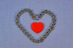 Coeur rouge encadré avec des chaînes sur un fond bleu Image libre de droits