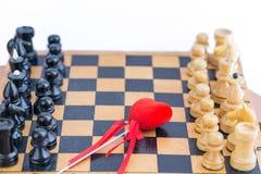 Coeur rouge entre deux composants d'échecs Photo libre de droits
