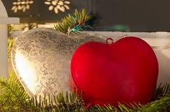 Coeur rouge et argenté sur un branchement de sapin Photos libres de droits