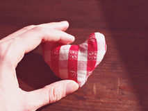 Coeur rouge et blanc de toile sur la table brune dans une main Photographie stock