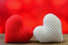 Coeur rouge et blanc sur la table en bois et le fond rouge Photos stock