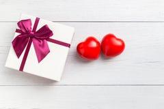 Coeur rouge et boîte-cadeau de vue supérieure avec le ruban sur le plan en bois blanc Images libres de droits