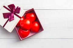 Coeur rouge et boîte-cadeau de vue supérieure avec le ruban sur le plan en bois blanc Photo libre de droits