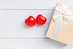Coeur rouge et boîte-cadeau de vue supérieure avec le ruban sur le plan en bois blanc Images stock