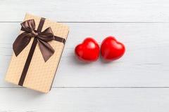 Coeur rouge et boîte-cadeau de vue supérieure avec le ruban sur le plan en bois blanc Image libre de droits