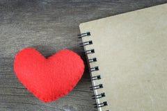 Coeur rouge et carnet brun vide placés sur un plancher en bois Image libre de droits