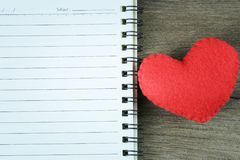 Coeur rouge et carnet vide placés sur un plancher en bois Image libre de droits