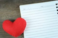 Coeur rouge et carnet vide placés sur un plancher en bois Photo libre de droits